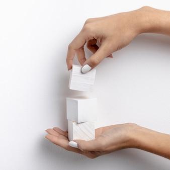 Close-upvrouw die een toren met kubussen bouwen