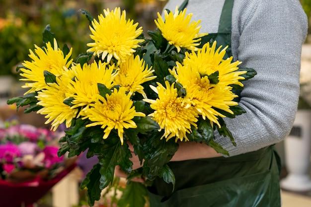 Close-upvrouw die elegante bloemen houden