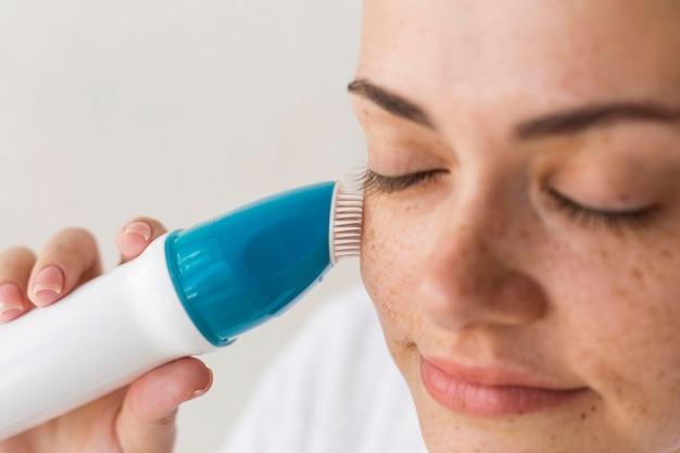 Close-upvrouw die gezichtsapparaat gebruikt