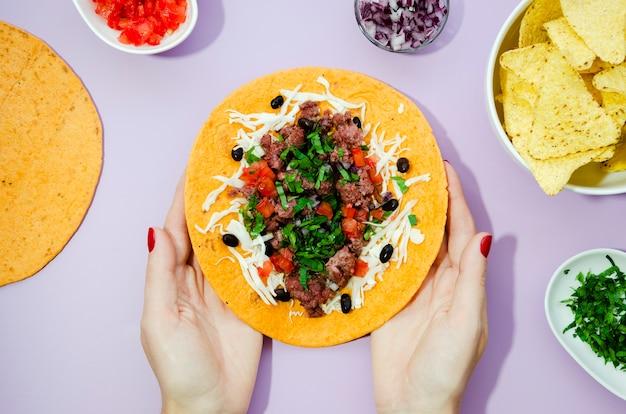 Close-upvrouw die grote ongevouwen burrito houden
