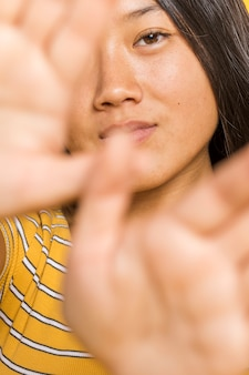 Close-upvrouw die haar gezicht behandelen met handen