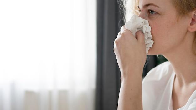 Close-upvrouw die haar neus blazen