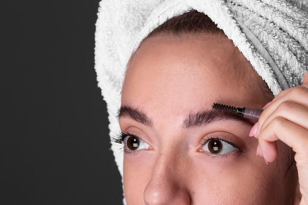 Close-upvrouw die haar oog doen brow