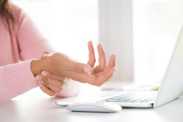 Close-upvrouw die haar polspijn van het gebruiken van computer houdt. office-syndroom