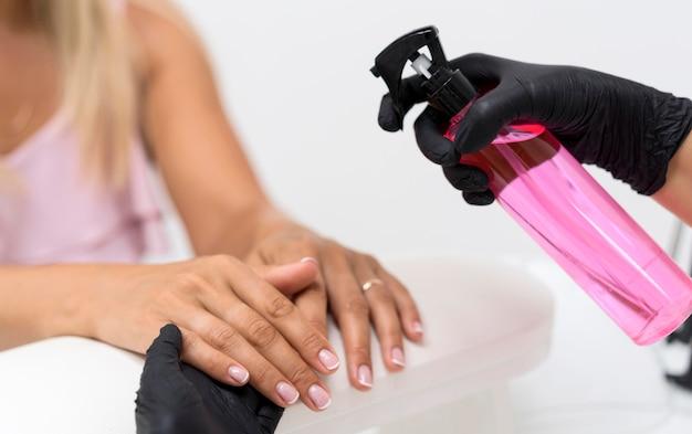 Close-upvrouw die handdesinfecterend middel gebruikt
