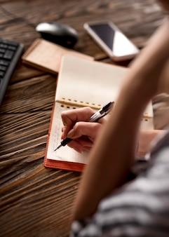 Close-upvrouw die in agenda schrijven
