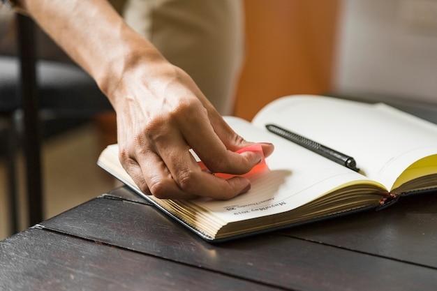 Close-upvrouw die kleverige nota op notitieboekje zetten