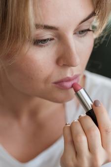 Close-upvrouw die lippenstift toepassen