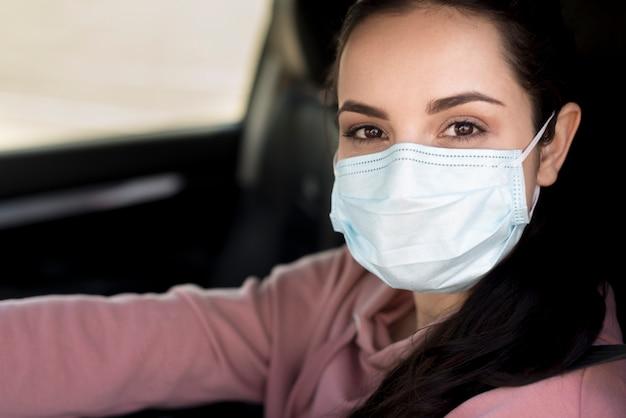 Close-upvrouw die masker binnen haar eigen auto dragen