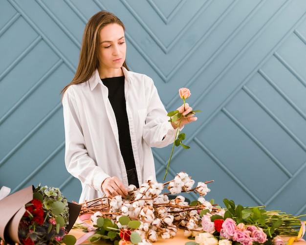 Close-upvrouw die met witte laag een bloem houden