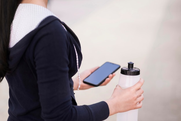 Close-upvrouw die mobiele telefoon en waterfles houden