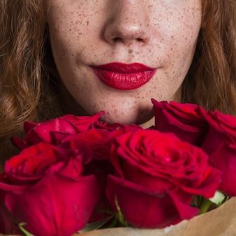 Close-upvrouw die mooie rozen ruiken