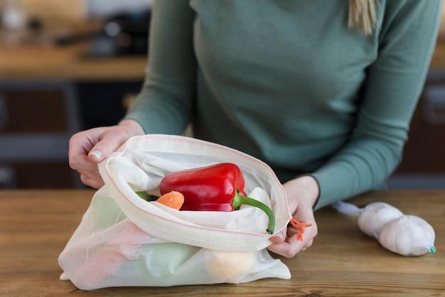 Close-upvrouw die opnieuw te gebruiken zak met groenten openen