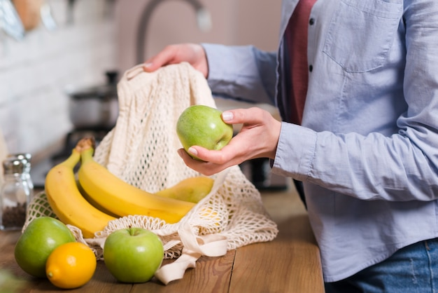Close-upvrouw die organische vruchten krijgen uit ecotas