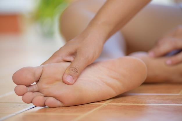 Close-upvrouw die pijn thuis in haar voet voelen. gezondheidszorg concept.