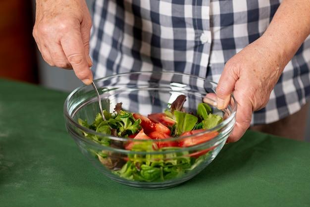 Close-upvrouw die salade mengen