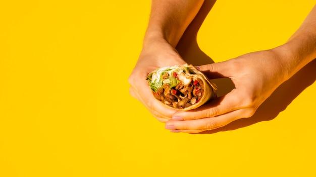 Close-upvrouw die smakelijke burrito houden