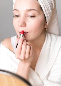 Close-upvrouw die spiegel gebruiken om lippenstift toe te passen