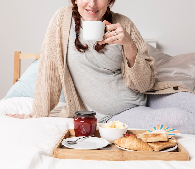 Close-upvrouw die van brunch in bed genieten