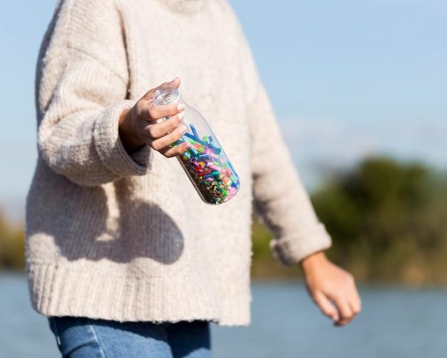 Close-upvrouw het plukken plastiek van kust