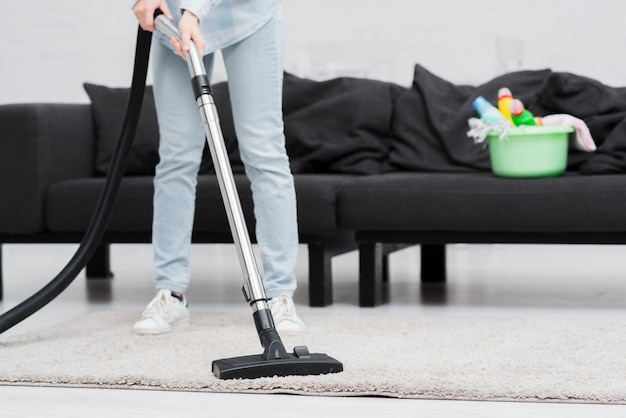 Close-upvrouw het schoonmaken met stofzuiger
