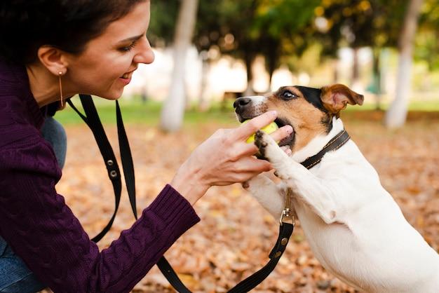Close-upvrouw het spelen met haar hond
