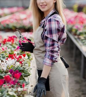 Close-upvrouw in serre met het tuinieren schaar