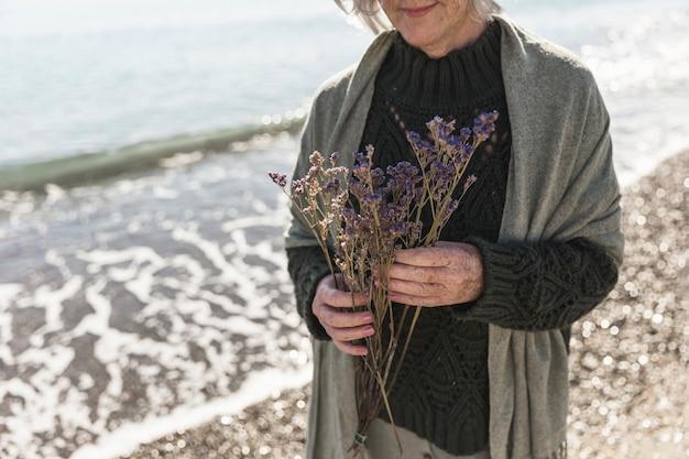 Close-upvrouw met bloemen op het strand
