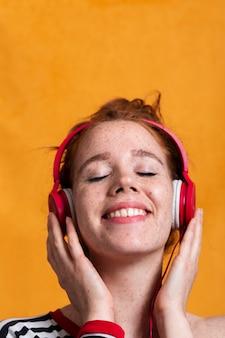Close-upvrouw met brede glimlach en hoofdtelefoons