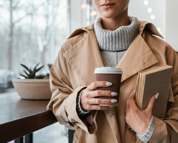 Close-upvrouw met kop en boeken