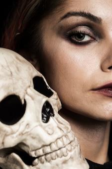 Close-upvrouw met menselijke schedel