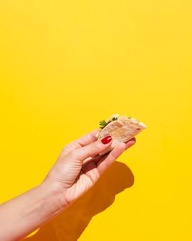 Close-upvrouw met taco en gele achtergrond