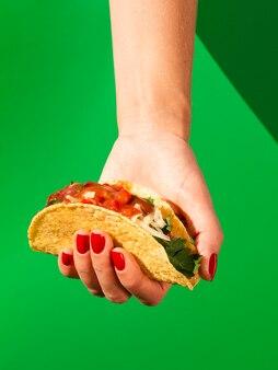 Close-upvrouw met taco en groene achtergrond