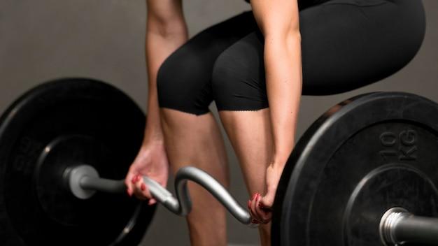 Close-upvrouw opleiding met gewichtheffenbar