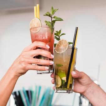 Close-upvrouwen die van cocktailglazen genieten