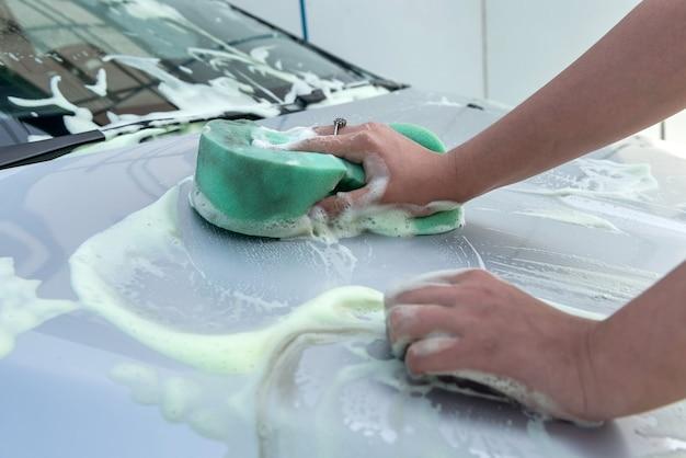 Close-upvrouwenhanden die groene spons met zeepschuim gebruiken die haar moderne auto wassen