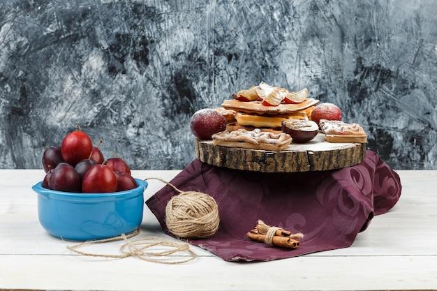 Close-upwafels en koekjes op ronde rieten placemat met een kom pruimen, bordeauxrood tafelkleed en kluwen op donkerblauw marmer en wit houten plankoppervlak. horizontaal