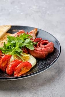 Close-upweergave van gebakken eieren met worst, spek, tomaten en bonen op een bord met toast