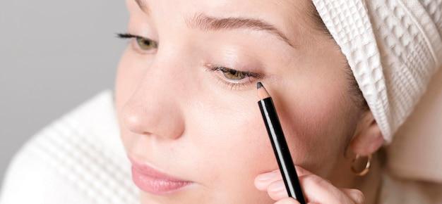 Close-upwijfje die eyeliner toepassen