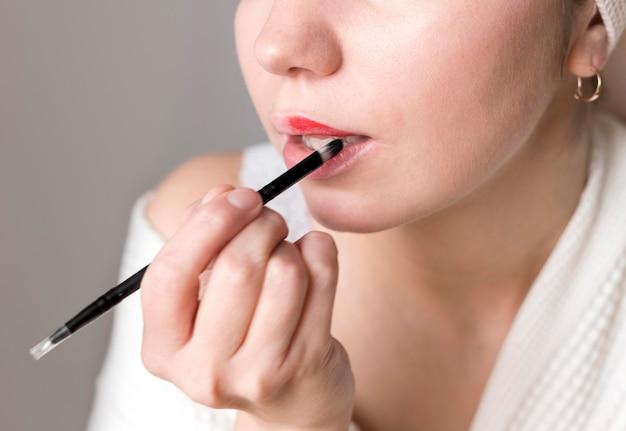 Close-upwijfje die lippenstift toepassen