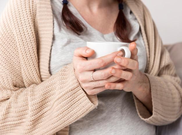 Close-upwijfje die van kop thee genieten
