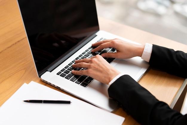 Close-upzakenman die aan laptop werken