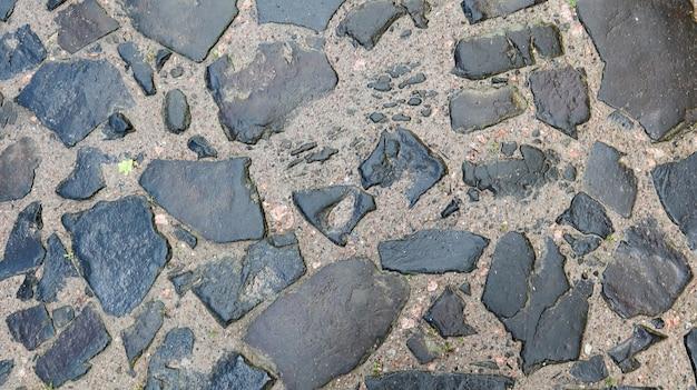 Closeup achtergrondstructuur van oude natte bestrating. een oude geplaveide weg voor je achtergrond. ruimte kopiëren. plat leggen.