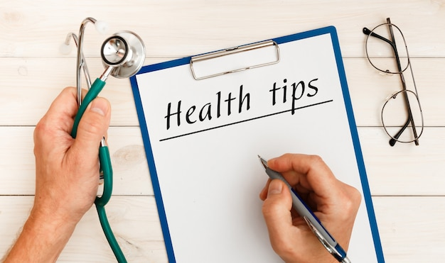 Closeup arts handen met witte kaart bord met gezondheid tips sms-bericht op ziekenhuiskliniek