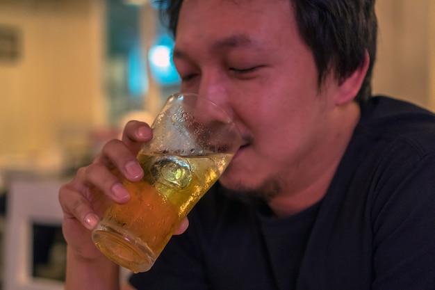 Closeup aziatische jongeman in geluk actie en bier drinken in de pub en restaurant