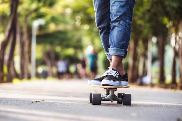 Closeup aziatische man spelen op surfskate of skate board in buiten park
