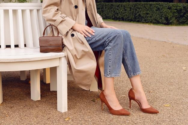 Closeup benen hoge hakken, vrouw in beige jas en blauwe spijkerbroek met bruine lederen tas. fashion street herfst outfit