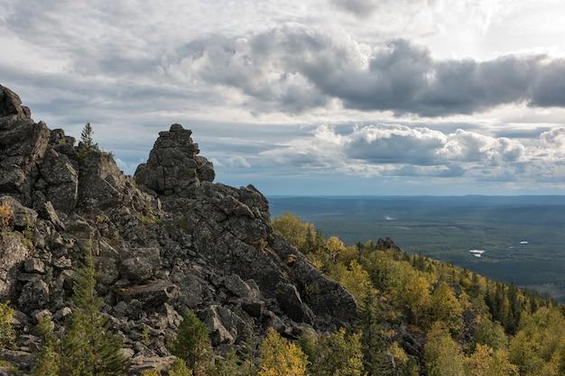 Closeup bergen scènes in nationaal park kachkanar, rusland, europa. bewolkt weer, dramatische blauwe kleur lucht, ver weg groene bomen