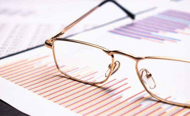 Closeup bril op financiële krant onder lichte tint blauw tint