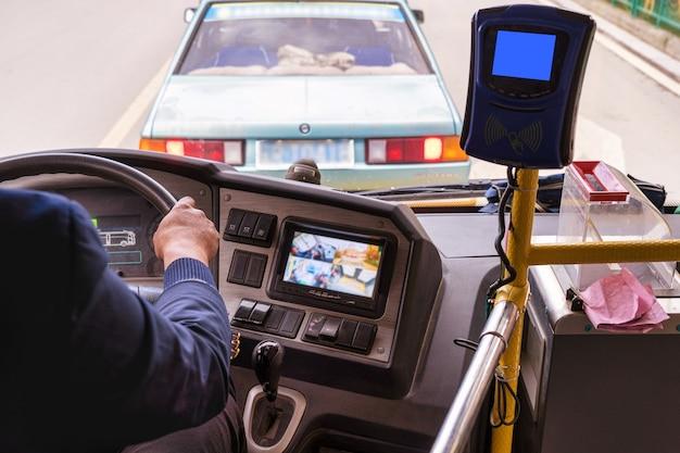 Closeup chinese chauffeur hand rijden de elektrische bus of ev rond de oude binnenstad van dukezong